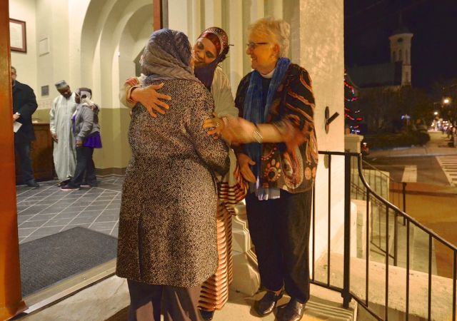 "Sister Munira Salim Abdalla of the Islamic Umma of Fredericksburg and Gay M. Rahn, an Associate Rector at St. George's Episcopal Church in Fredericksburg, Va., greet a guest to a ""Prayer Vigil for Unity."""